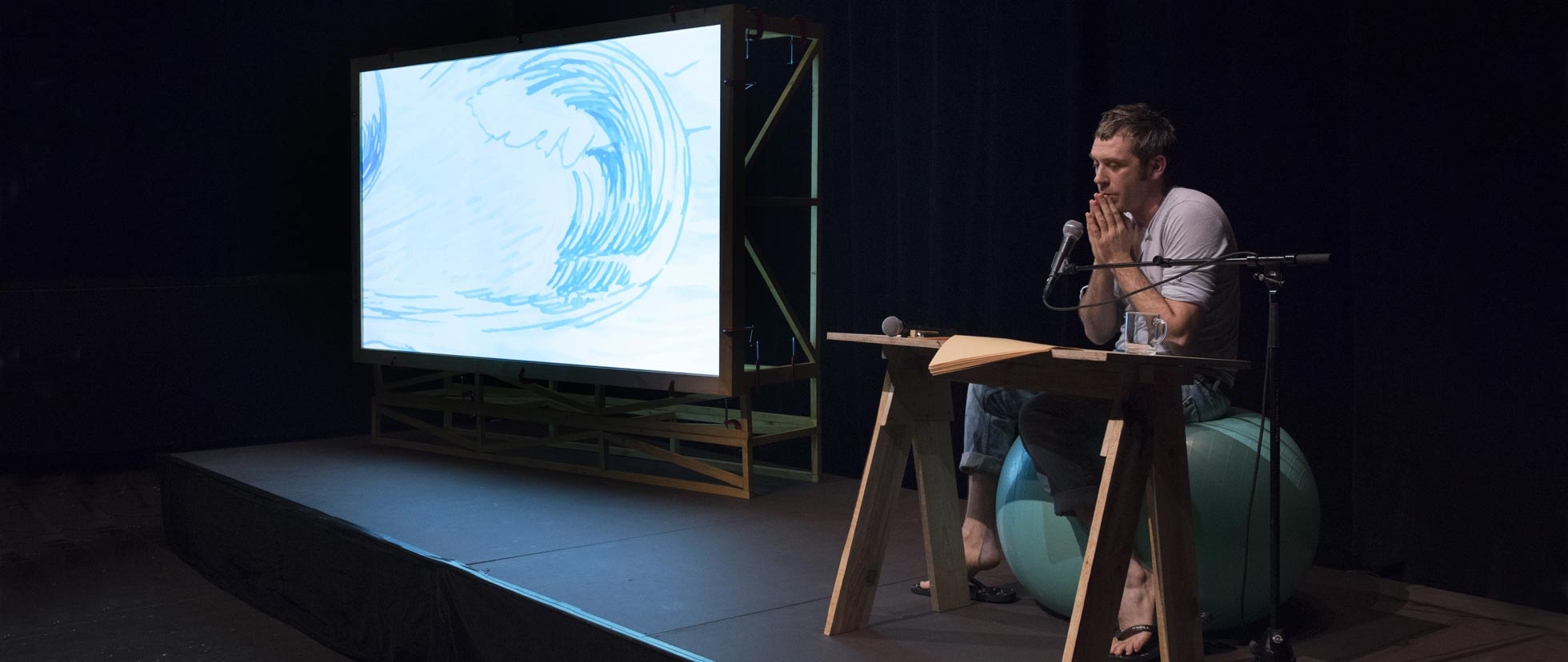 Julien Fournet seated behind a desk on stage next to a projection screen